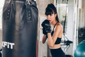 woman in boxing gloves focus on punching bag
